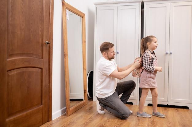 Молодой отец надевает маленький рюкзак на спину своей симпатичной маленькой дочери, помогая ей собирать вещи перед школой в коридоре