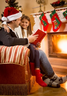 Young father reading book to daughter sitting at fireplace