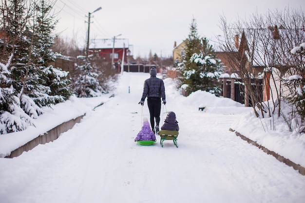 Young father rolls his little cute daughters on a sled in the snow outdoors