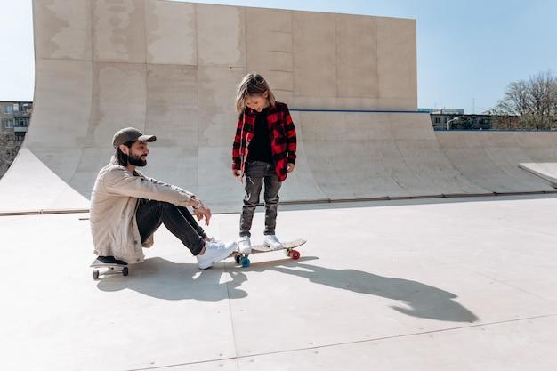 젊은 아버지는 스케이트보드에 앉고 그의 어린 아들은 화창한 날 야외에서 슬라이드가 있는 스케이트 공원에서 스케이트보드 위에 서 있습니다.