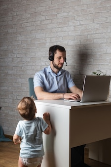 Молодой отец сидит за столом и работает на ноутбуке, присматривая за своими детьми и кошкой дома.