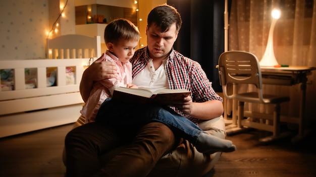Молодой отец сидит в спальне со своим маленьким сыном и читает книгу сказок. концепция воспитания детей и семьи, проводящей время вместе в ночное время.