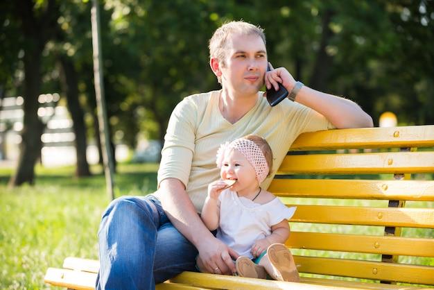ビスケットを食べる小さな娘と一緒にベンチに座っている若い父親
