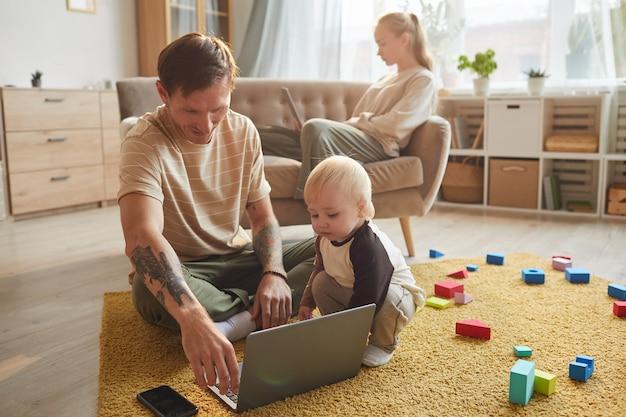 床に座って、母親と息子と一緒にラップトップで漫画を見ている若い父親