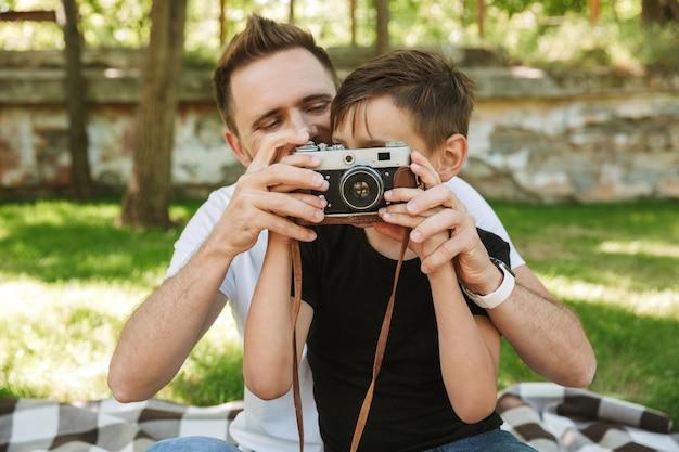 Молодой отец сидит с маленьким сыном, держа камеру фотографирования.