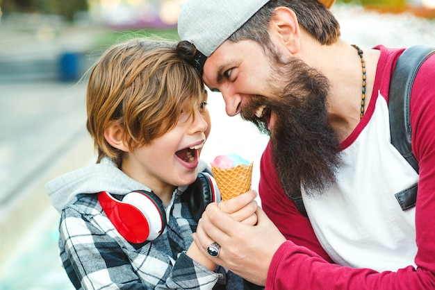 Young father and son enjoying icecream and having fun together. happy emotional family outdoors. vacation, summer time, walking at city. father playfully tries to eat icecream