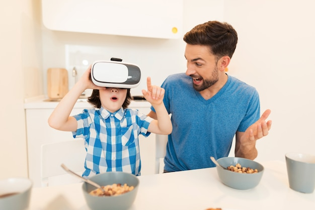 Young father and son using vr glasses at home.