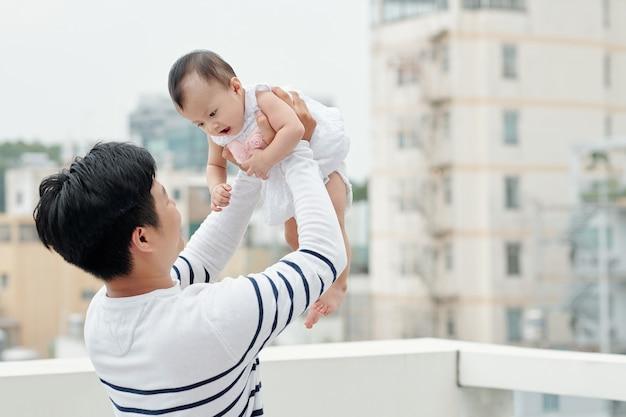 그의 작은 딸과 함께 시간을 보내고 즐겁게 그녀를 공중에서 들어 올리는 젊은 아버지