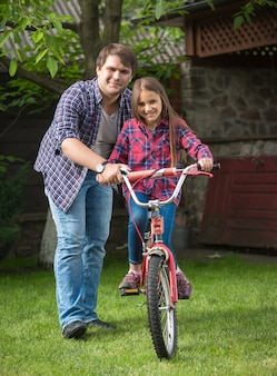 Young father teaching his daughter how to ride a bicycle at park