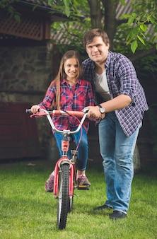 娘に自転車の乗り方を教える若い父親