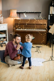 Young father teaching his little daughter to play guitar while sitting on the floor in the room