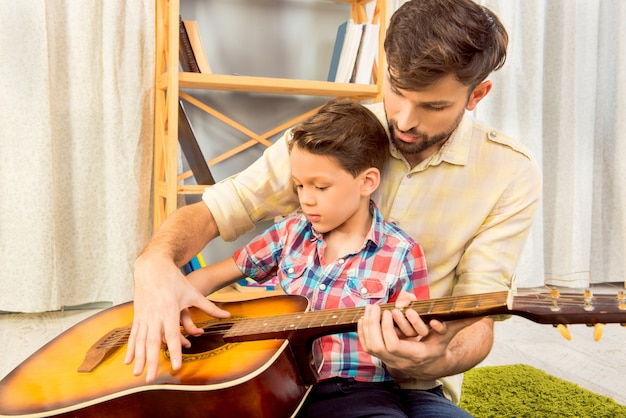 Young father teaching his little son to play on guitar