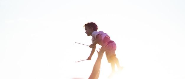 若い父親がかわいい息子を新鮮な空気の中で投げます。父の日、父と息子の男の子が屋外で遊んでハグします。