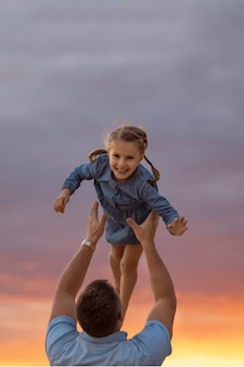 Young father throws up his cute and little daughter in the air on beach on sunset