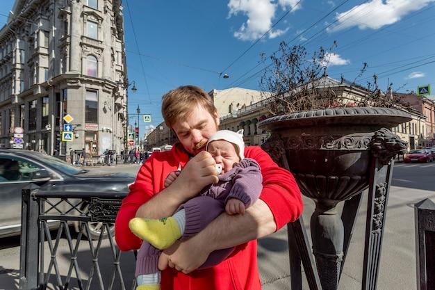 路上で彼の小さなかわいい赤ちゃんに追いつくことを試みている若い父親