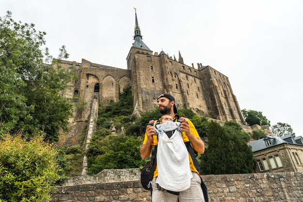 A young father visiting the famous mont saint-michel abbey in the manche department, normandy region, france