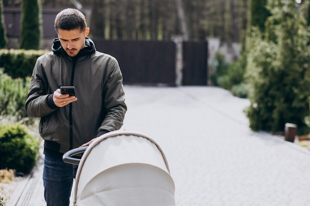 Young father walking with baby carriage in park