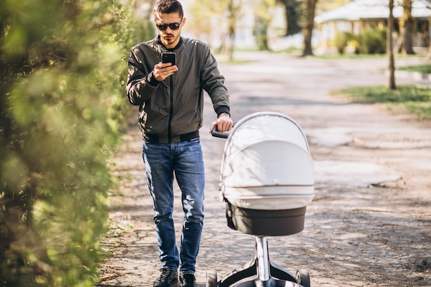 Young father walking with baby carriage in the park