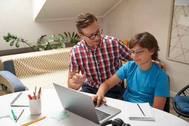 Молодой отец в очках помогает сыну с домашним заданием мальчик с ноутбуком