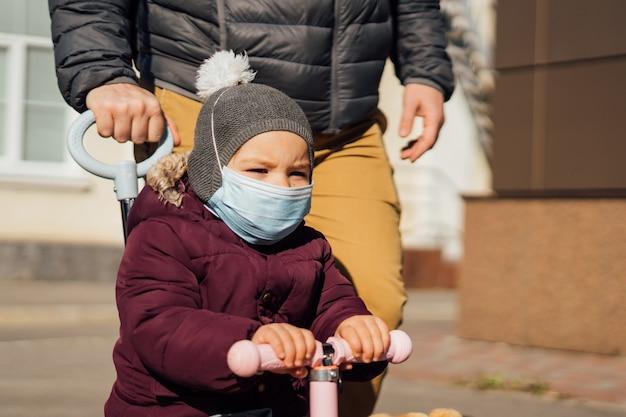 Молодой отец с ребенком на самокате гуляя снаружи в медицинские маски. загрязнение воздуха, пандемический вирус