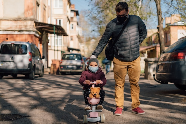 Young father with child on scooter walking outside in medical masks.