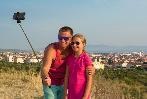 屋外で自分撮りをしている娘と若い父