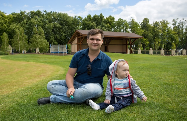 공원에서 푸른 잔디에 편안한 그의 9 개월 된 아기와 젊은 아버지