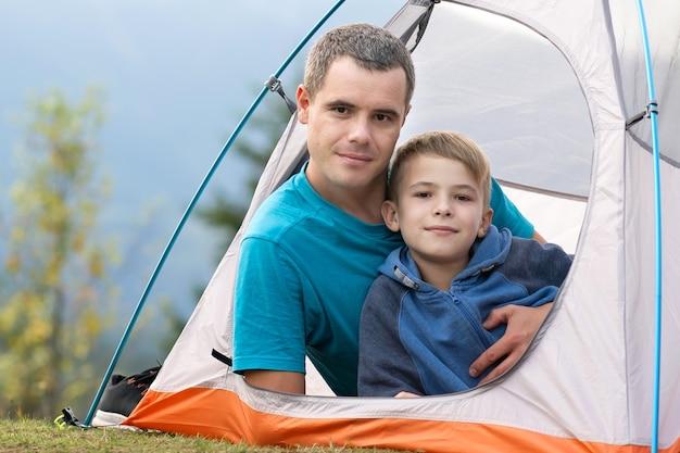 여름 산에서 캠핑 텐트에서 함께 쉬고 그의 자식 아들과 함께 젊은 아버지. 활동적인 가족 레크리에이션 개념입니다.