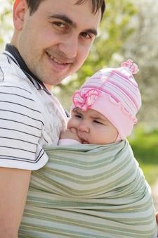 スリングで彼の5ヶ月の娘を持つ若い父親