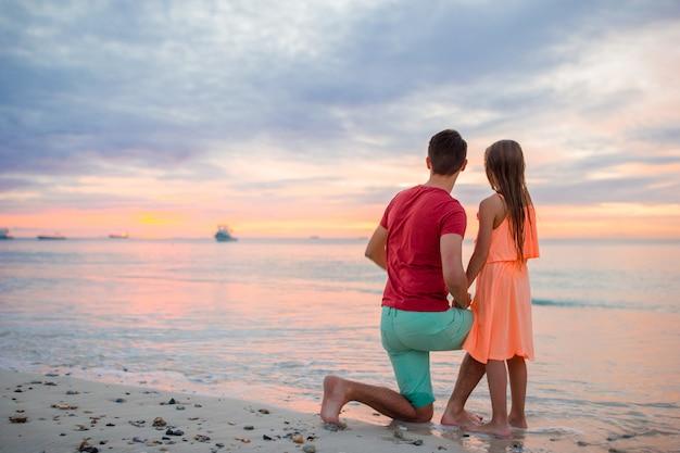 エキゾチックなビーチで夕日を見ている彼の小さな子供を持つ若い父親