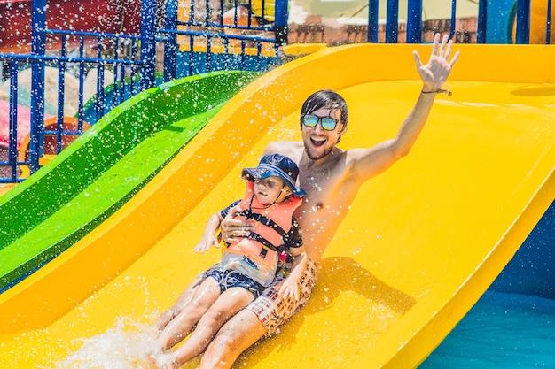 Молодой отец с маленьким сыном скатываются с водной горки в аквапарке в яркий солнечный летний день в окружении множества брызг