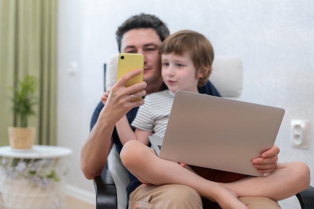 Молодой отец с сыном, используя ноутбук и смартфон.
