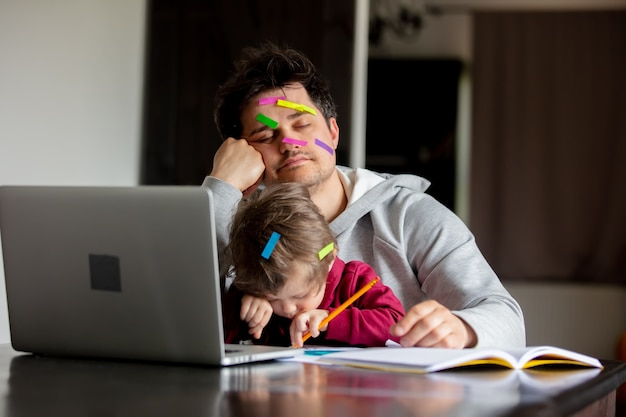 Young father works at a computer at home with a child