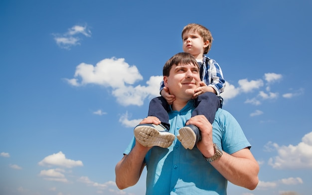 Young fatherand a little son on a sky background
