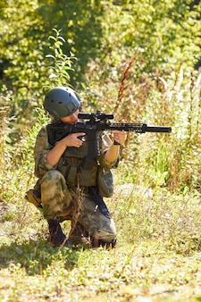 Young fearless soldier woman poiting rifle at side at enemy in the forest