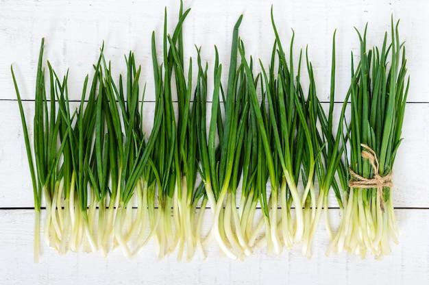 흰색 나무 테이블에 녹색 양파의 어린 깃털 (잎)이 묶여 흩어져 있습니다. 평면도. 첫 번째 봄 나물. 샐러드 재료.