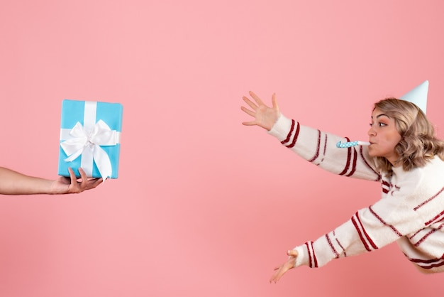 Молодая женщина принимает подарок от мужчины на розовом