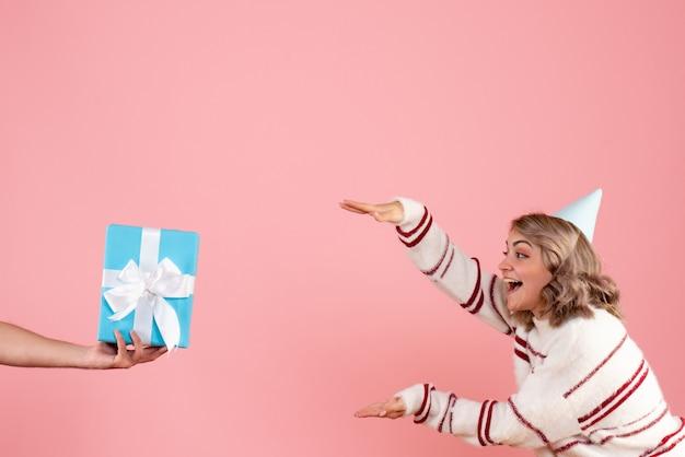 ピンクの男性からのプレゼントを受け入れる若い女性