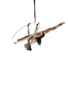 白いスタジオの背景トレーニングで分離された若い女性のアクロバットサーカスアスリートは完璧にバランスが取れています