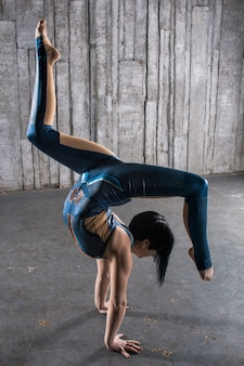 Young female acrobat standing on hand over gray background in photo studio. flexible woman circus gymnast, gymnastics handstand.