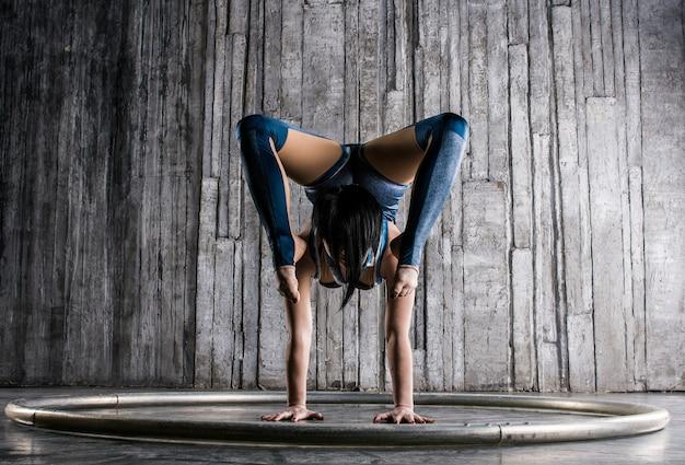 Молодая женщина-акробат, стоя на руке над серой поверхностью в фотостудии