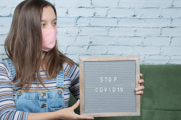 Covid 관련 포스터를 들고 있는 젊은 여성 활동가