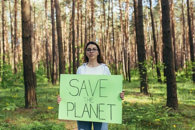 ポスターを持って森の中に立っている若い女性活動家が地球を救う、ボランティアが森林破壊に苦しんでいる