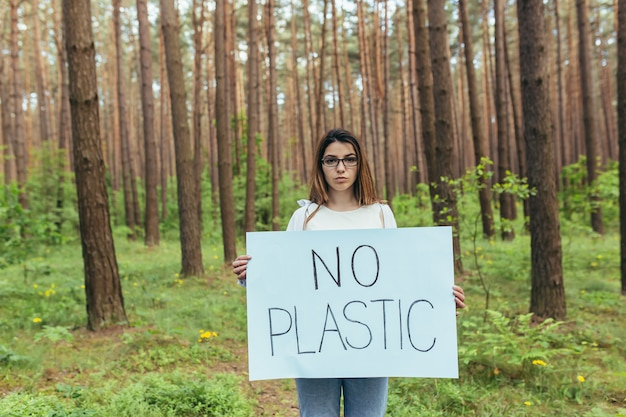 プラスチックのポスターなしで森の中に立っている若い女性活動家、森林汚染に苦しんでいるボランティア