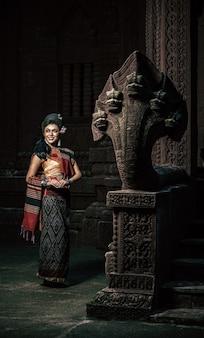 Giovane attrice femminile che indossa bellissimi costumi antichi, in monumenti antichi, in stile drammatico. esibisciti in una leggenda popolare storia d'amore, racconto popolare thai isan chiamato