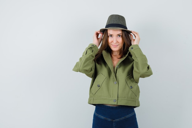 Young female adjusting her hat in jacket, pants and looking cute. front view.