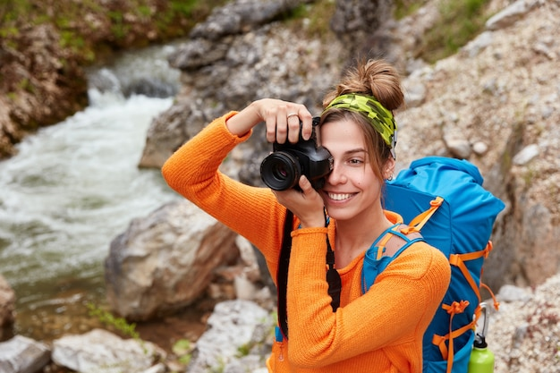 Young female adventurer poses against small river in ravine, holds camera