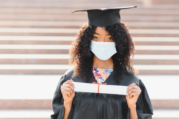 若い女性のアフリカ系アメリカ人の大学院生は、コロナウイルスに対する保護マスクを着用しています