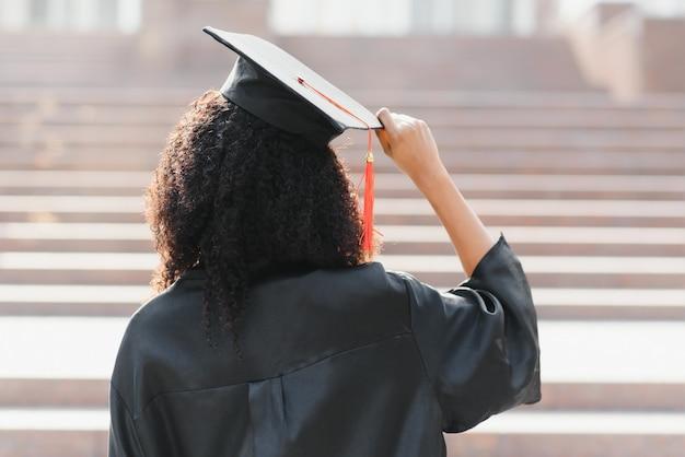 Молодая афро-американская студентка с дипломом позирует на открытом воздухе.