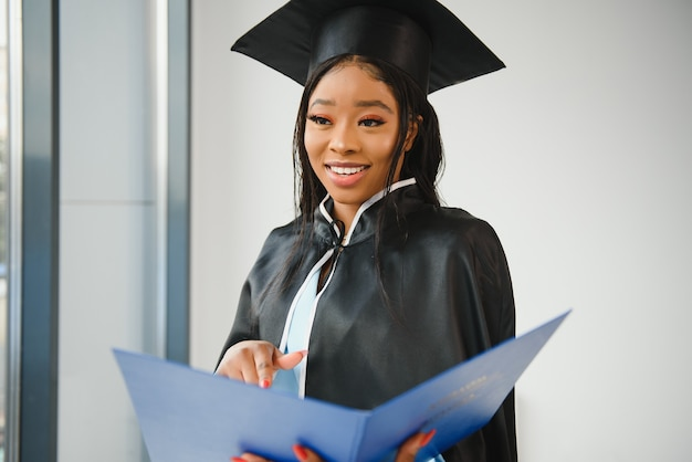 Молодая афро-американская студентка с дипломом.